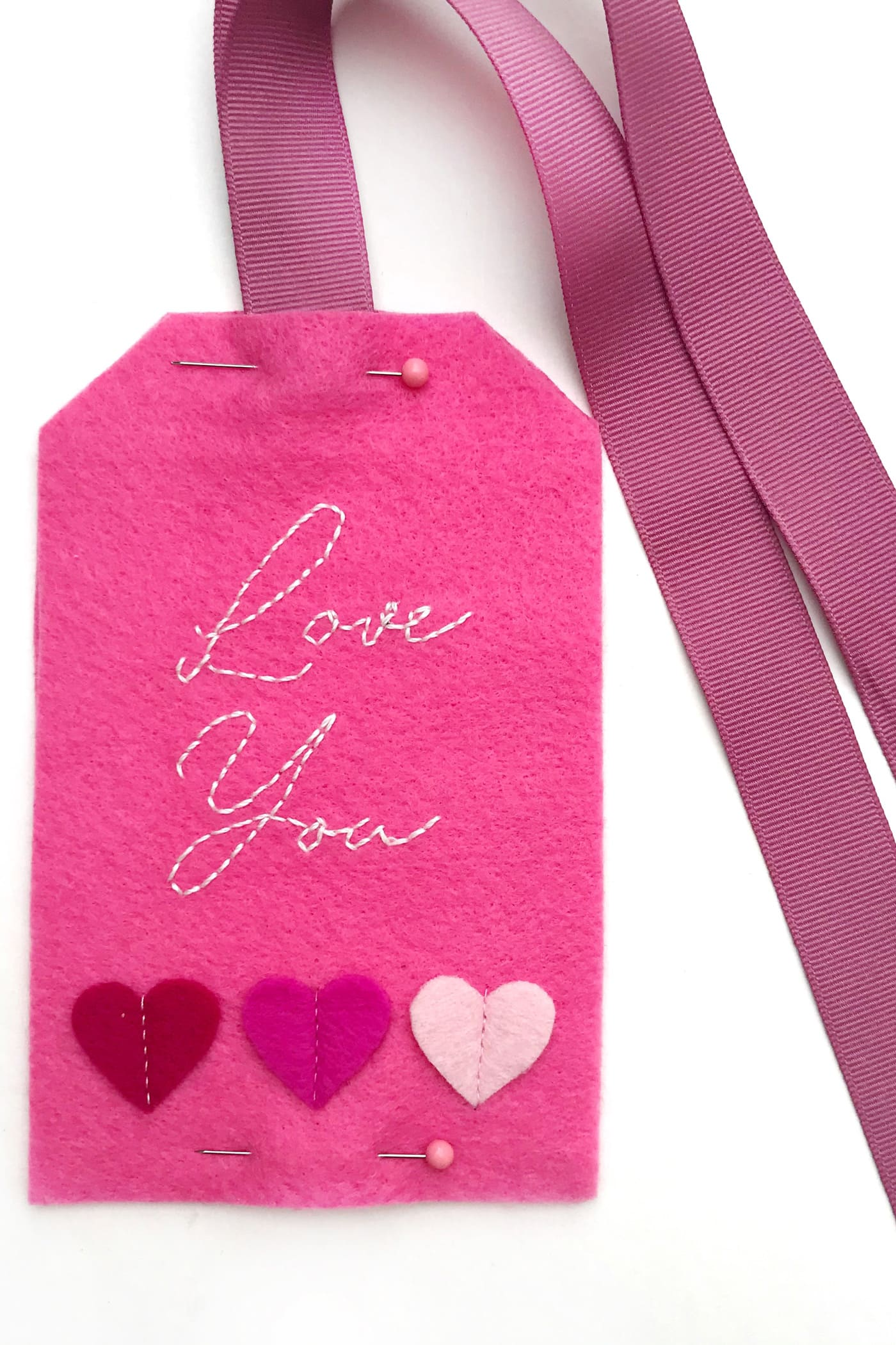 hand embroidered felt gift tags on white table showing ribbon attachment process