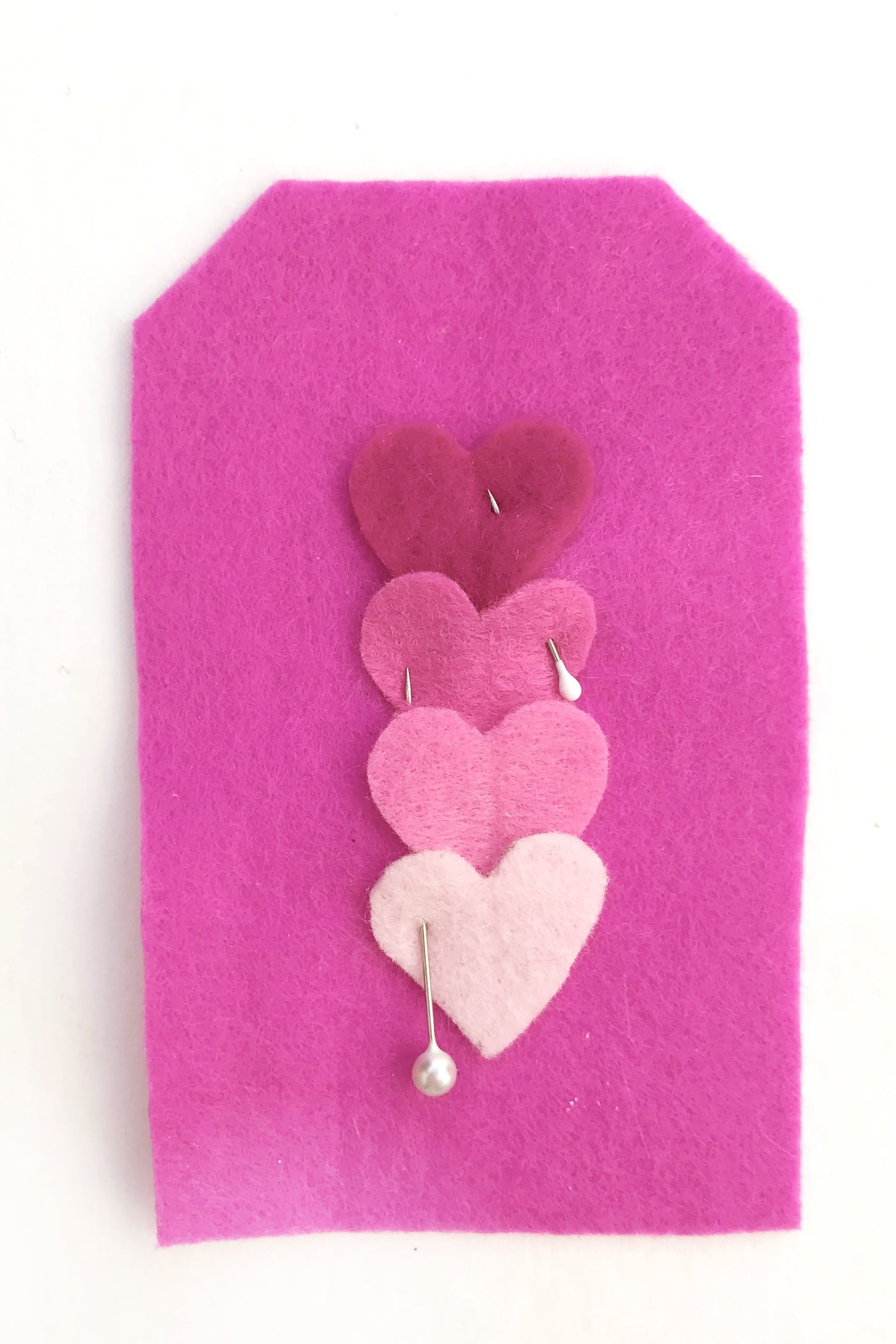 hand embroidered felt gift tags on white table with hearts pinned on