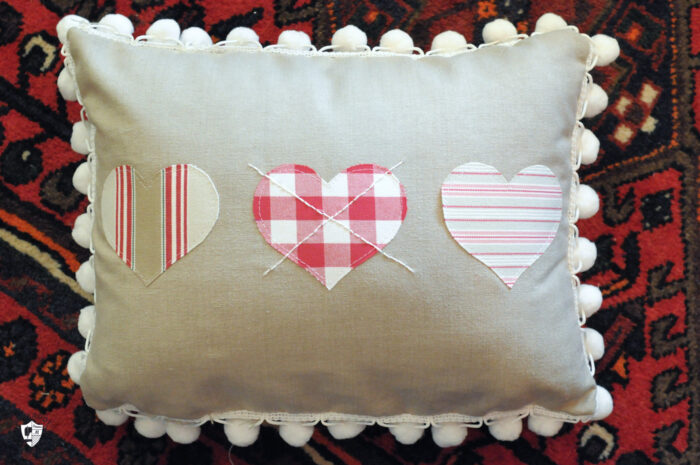 Linen colored heart pillow on red rug