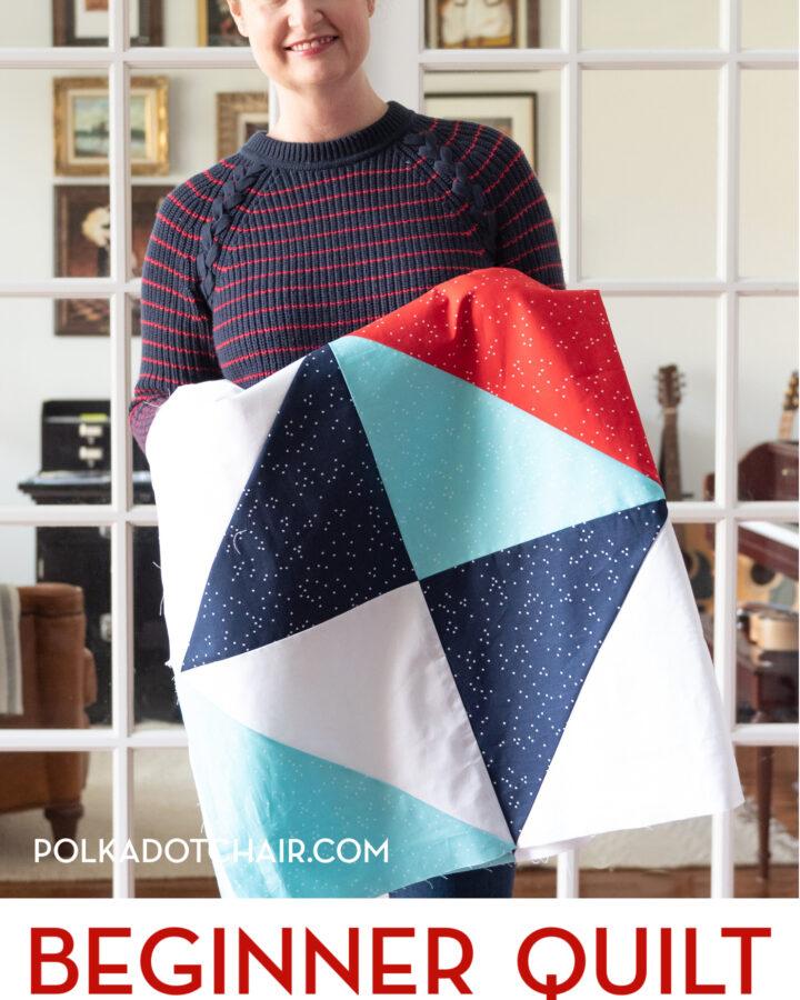 woman holding quilt top in front of door