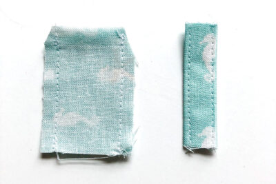 rectangles of fabric cut out and sewn on white tabletop