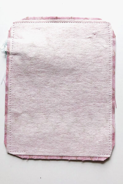 two pieces of pink fabric wrong side out on white table