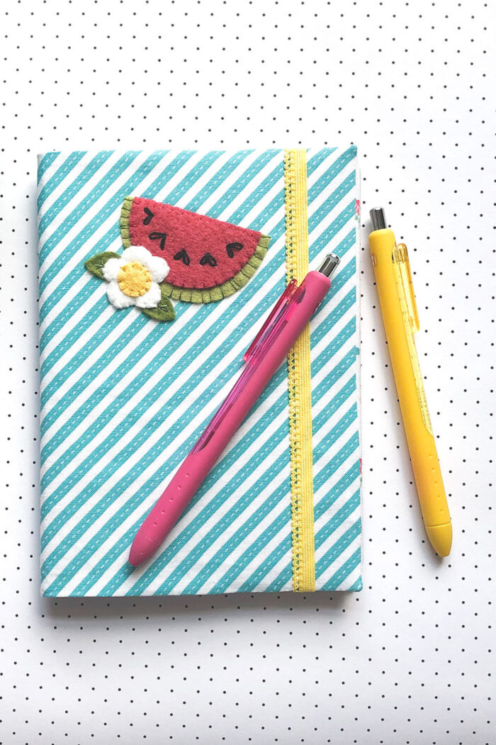 blue and white striped note book on white & black polka dot tablecloth