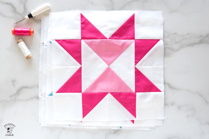 summer sunsets pink quilt block on white marble table with pink cutting mat
