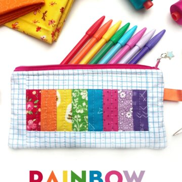 rainbow pencil pouch on white table with spools of thread and fabric