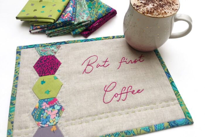 tan and jewel tone mug rug on white table with coffee and fabric