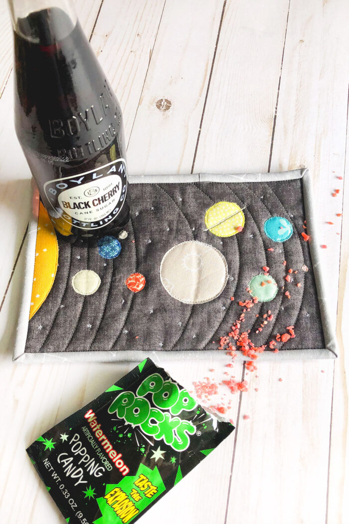 Colorful fabric Solar System mug rug on white wood table