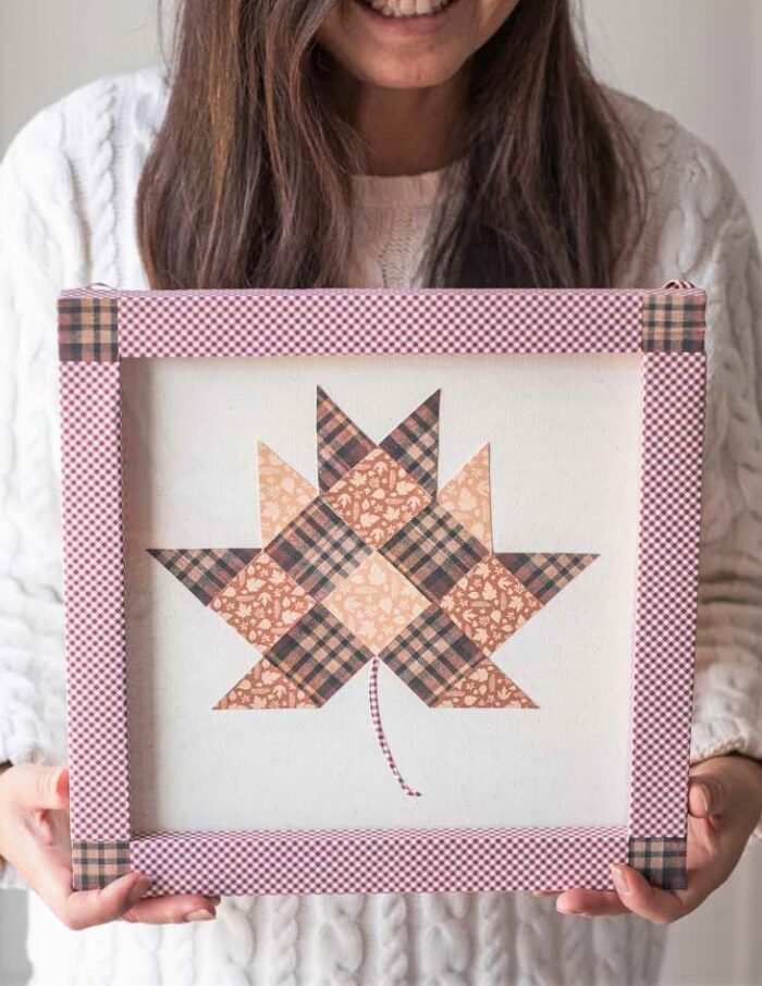 Paper quilt block leaf art held by woman in white sweater