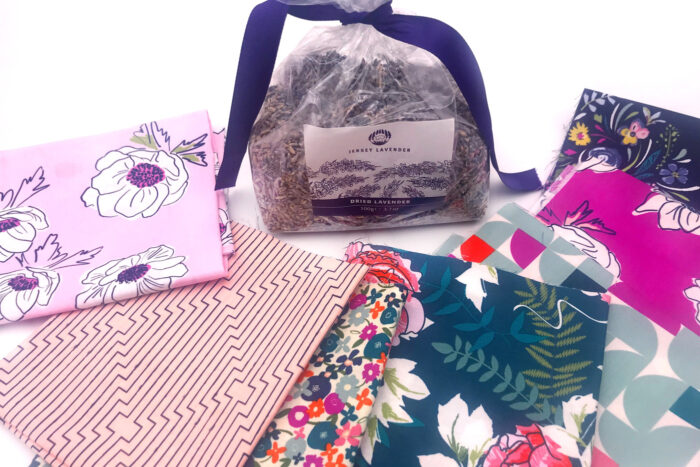stacks of fabric and bag of lavender on white table