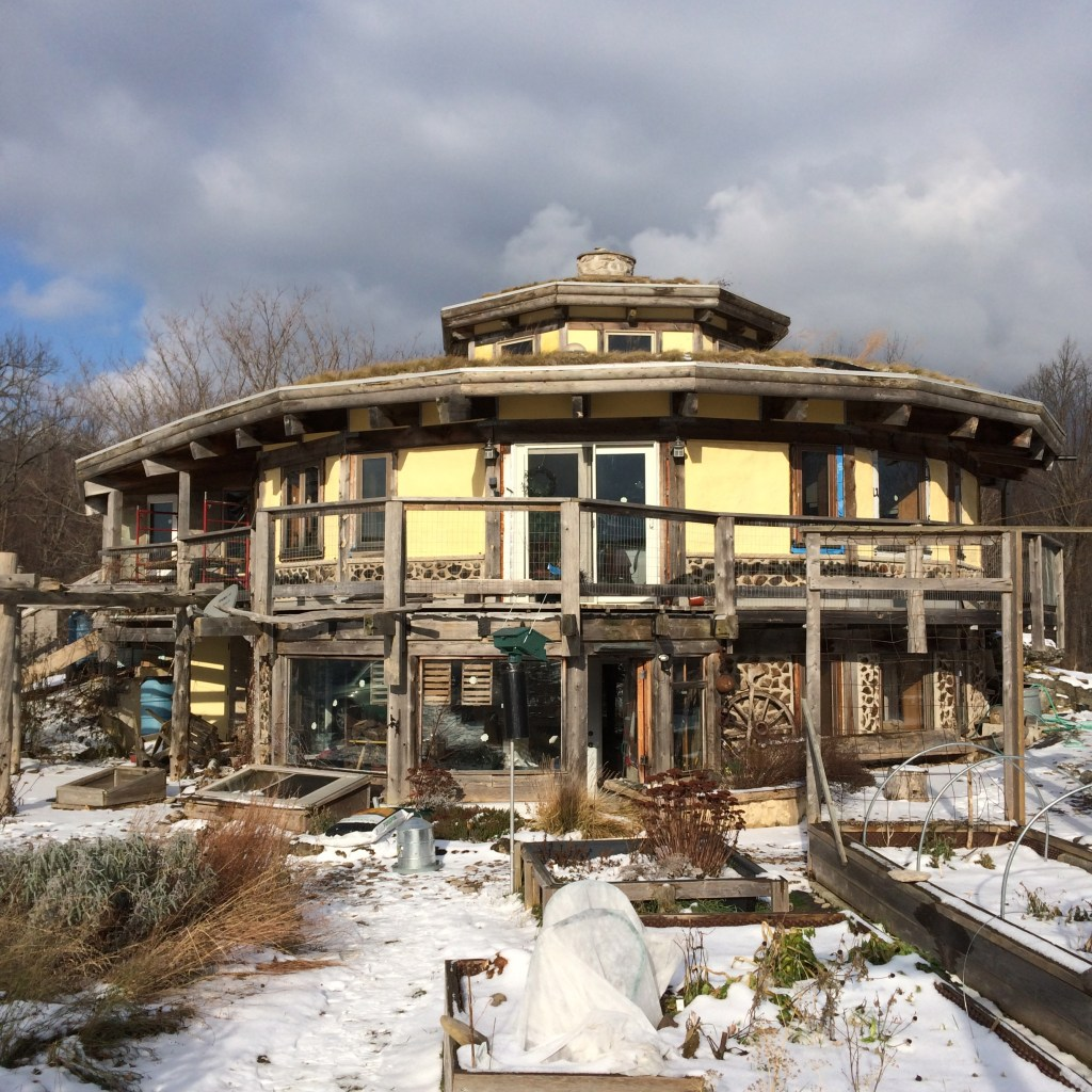 Cordwood, straw bale, post and beam homestead on a sunny winter day