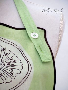 Close up of neck strap and 2 button holes for adjustable length.