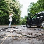 young-woman-standing-by-the-damaged-car-after-a-SHE6YK7