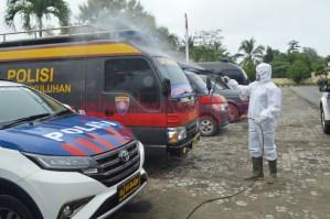 Petugas sedang menyemprotkan cairan desinfektan pada mobil dinas