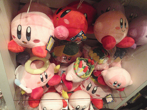a store display of many stuffed plush toys of Kirby, the pink Nintendo game character