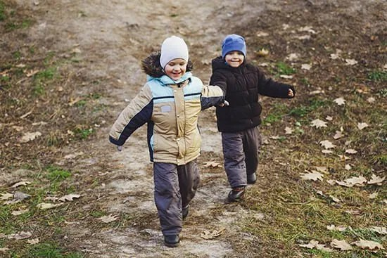 two kids running with coats and hats on