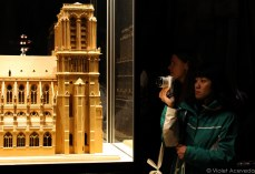 Crowding around a model of Notre Dame in a side chapel of the cathedral. © Violet Acevedo