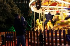 A dad and son watches the carousel at the Christmas carnival and market. © Violet Acevedo