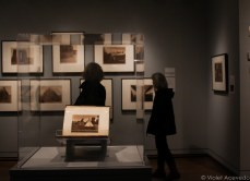 Women gazing at Edward Curtis's photographs of Native American culture. © Violet Acevedo