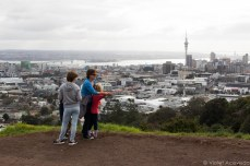 Mother pointing out the cardinal directions as the family gaze at downtown Auckland from the top of Mt. Eden. © Violet Acevedo