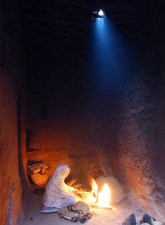 girl baking traditional bread in fire Morocco