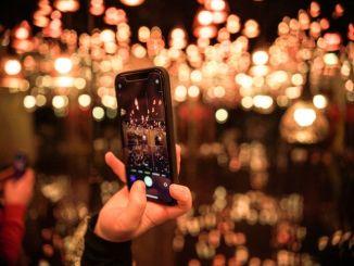 Une personne prenant des photos avec son smartphone avec des bokeh en arrière-plan.