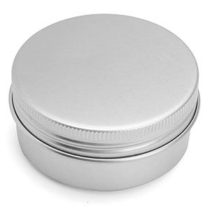 Three quarter view of a round silver tin with a ribbed edge along the lid.