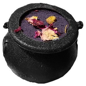 Small plastic cauldron filled to the top with a compacted black bath bomb mixture. There are dried rose petals on the top of it, scattered.