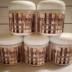 """Stack of 5 jars of whipped body butter. The label shows a sketch style forest in sepia and the lettering is made to look like trees. It says """"Into The Woods Whipped Body Butter"""" in brown text."""