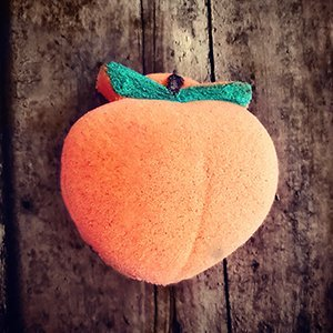 Bath bomb that looks like a peach, colored orange and pink with green leaves