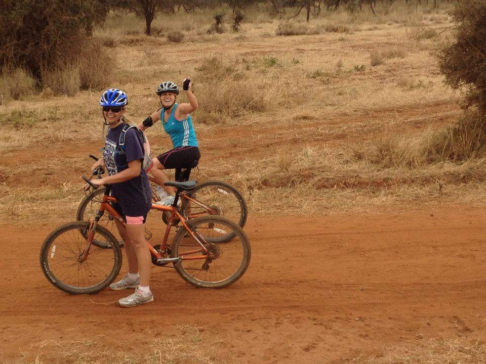 cyclists cycling through Kenya waving