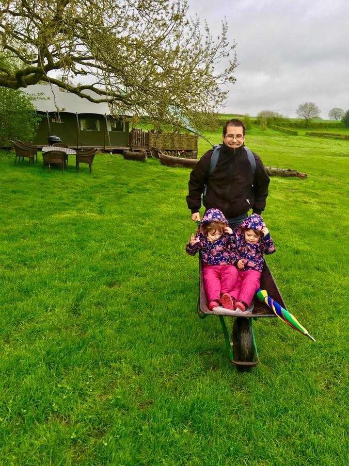 twins in a wheelbarrow in the rain at the Dandelion Hideaway Glamping