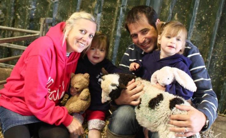 family with twin girls holding a lamb at North Bradbury farm