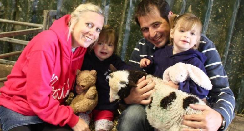 family with twin girls holding a lamb at North Bradbury farm