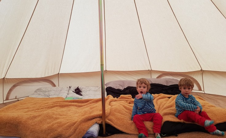 Twin boys sat inside tipi tent