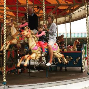 fair ground at Butlins just for tots weekend. Carousel with family riding the horses