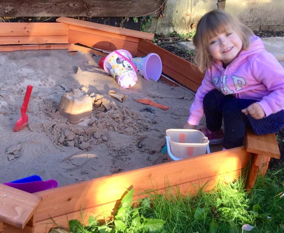 child sitting on the edge of the sandpit playing with the sand