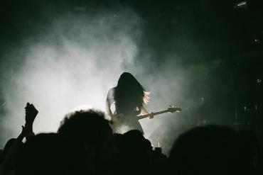 Mann mit E-Gitarre auf einer Bühne