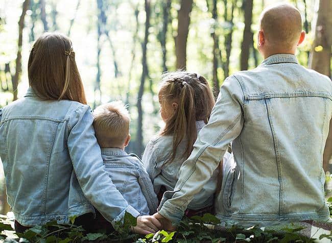 Junge Eltern sitzen mit ihren Kindern im Wald