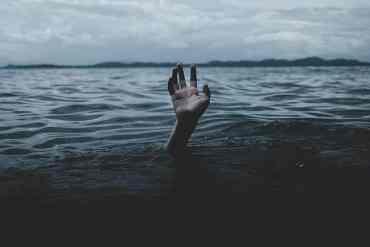 Hand streckt sich aus dem Meer