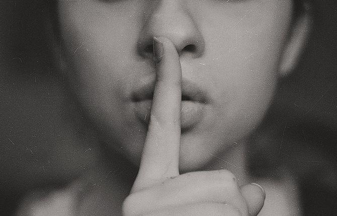Frau hält sich einen Finger vor den Mund