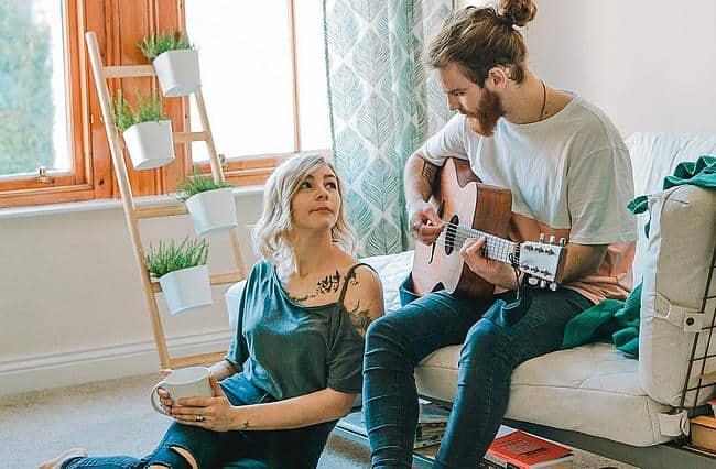 Mann spielt Gitarre, Freundin schaut zu