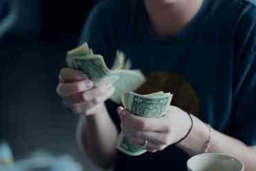 Frau zählt Geldscheine