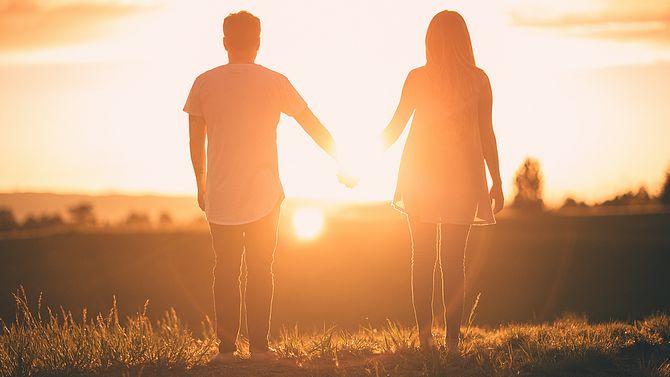 Paar hält Händchen und schauen in die Ferne