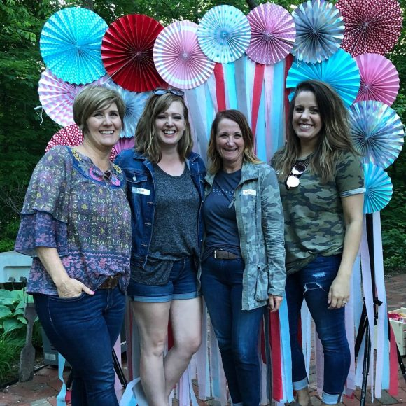 four women posing in front of a colorful streamer background at a summer event