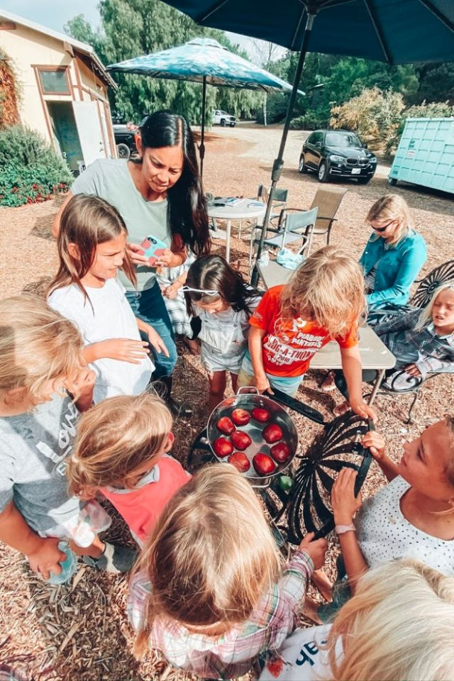 Girls bobbing for apples for a fall themed party | Poplolly co
