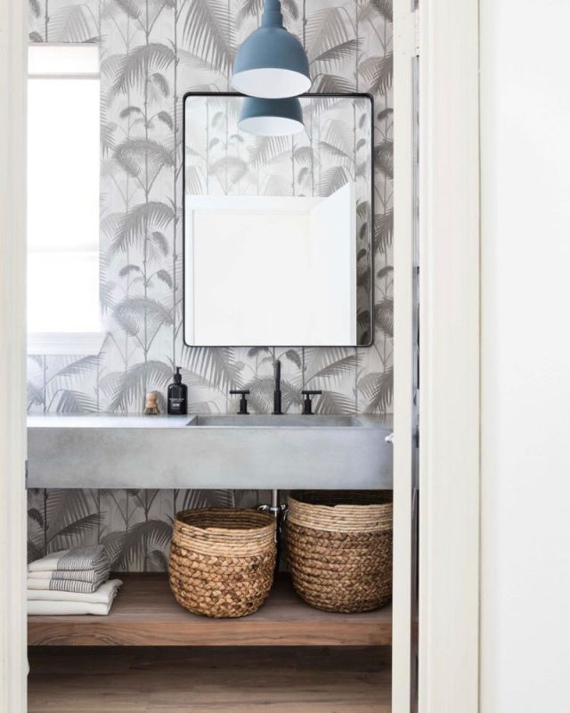 black white modern palm wallpaper in bathroom with cement floating vanity and baskets | Poplolly co