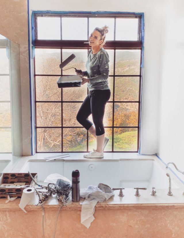 girl painting bathroom | how to brighten a beige travertine tile bathroom | Poplolly co