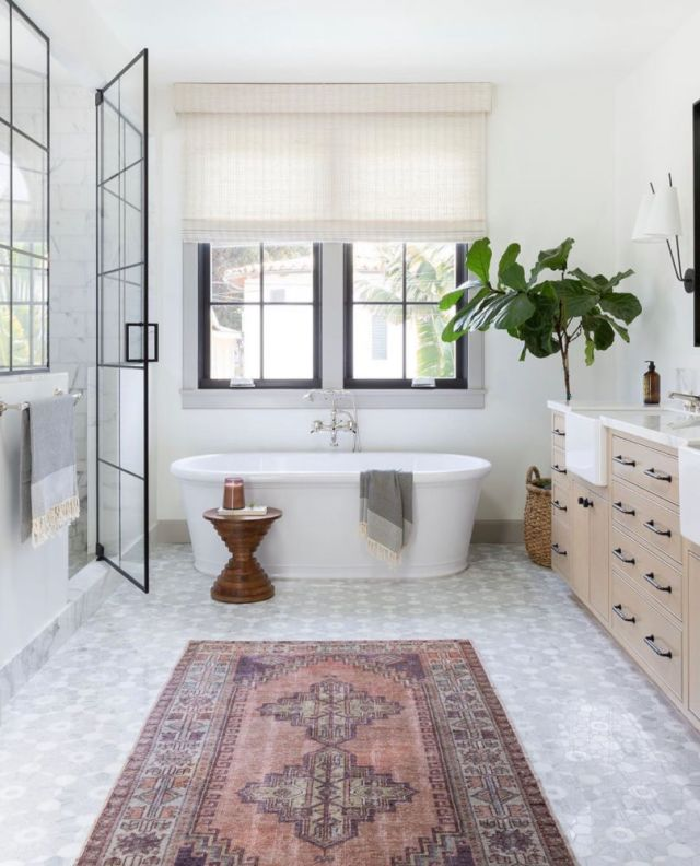 patterned tile, freestanding tub in front of window, black shower doors, white oak bathroom vanity with colorful rug | Poplolly co