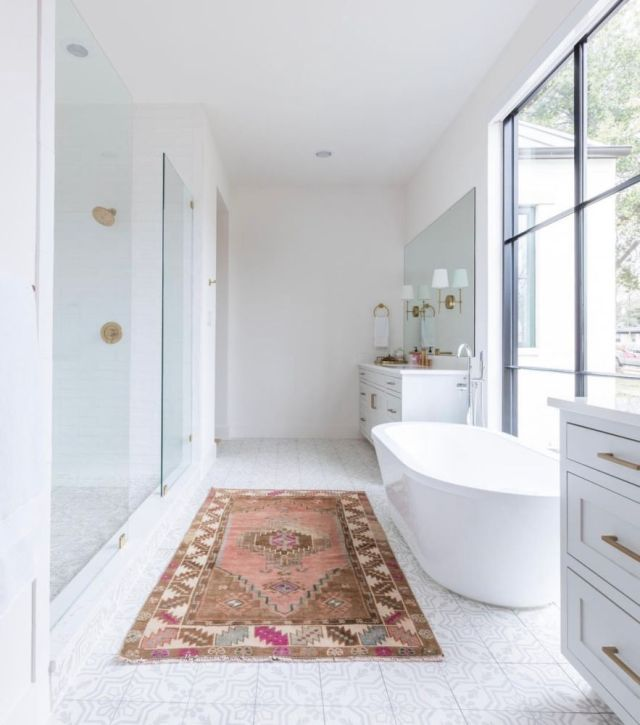 white tile bathroom with floating freestanding tub, bass fixtures and bright rug | Poplolly co