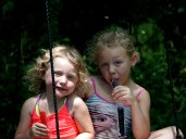 Youngest granddaughters swinging with popsicles.